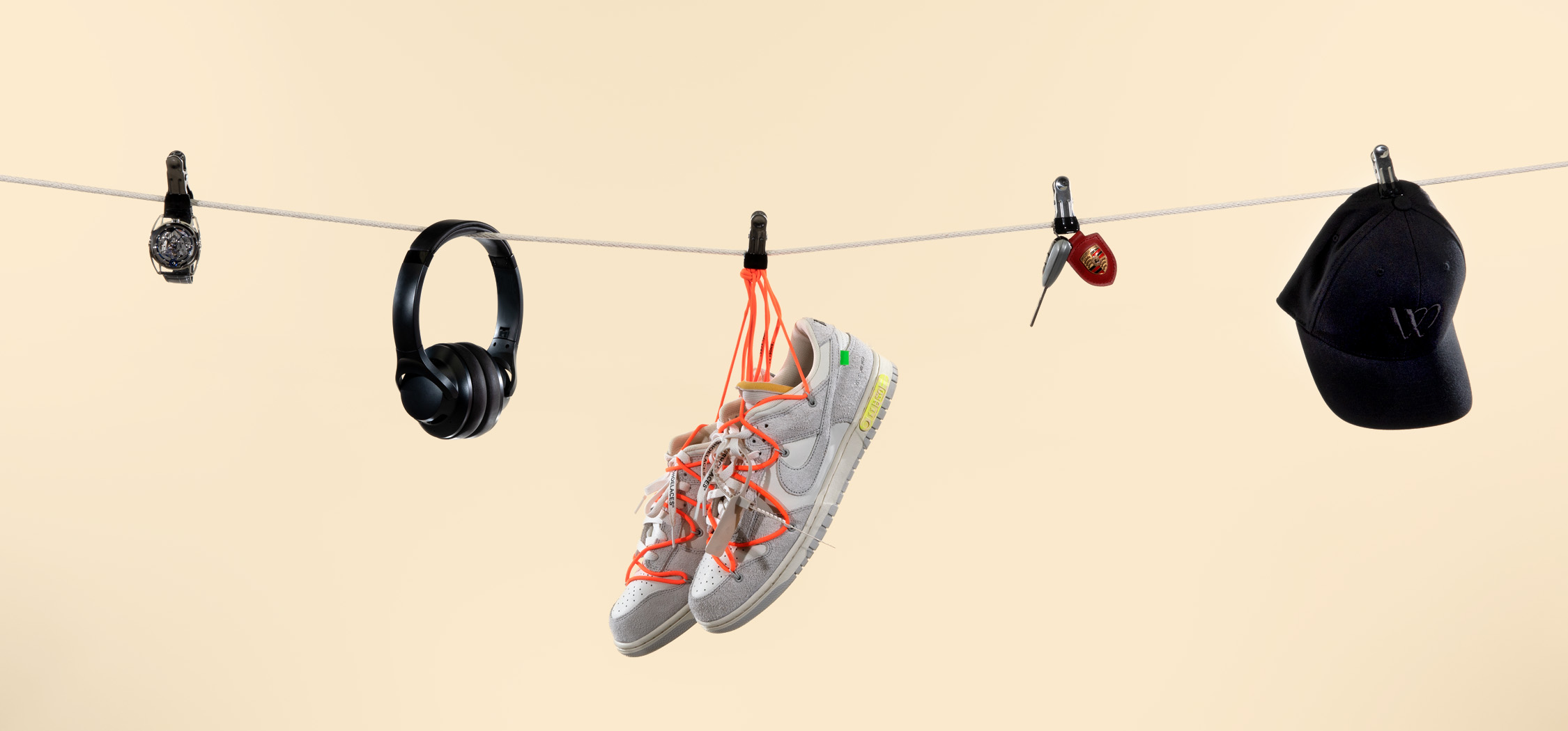Watch, headphones, sneakers, car keys, and WatchBox hat hanging from a clothesline